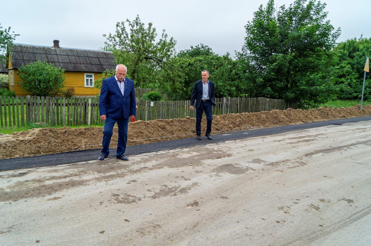 Dwóch mężczyzn stojących naremontowanej drodze