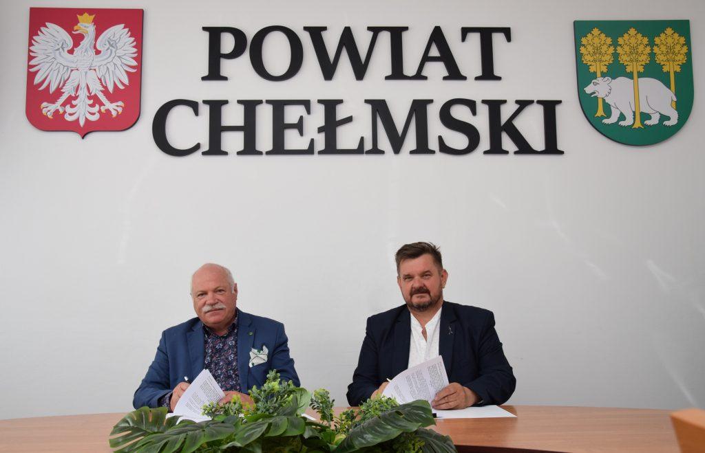 Dwie osoby siedzące przy stole, nadnimi znajduje się napis: Powiat Chełmski