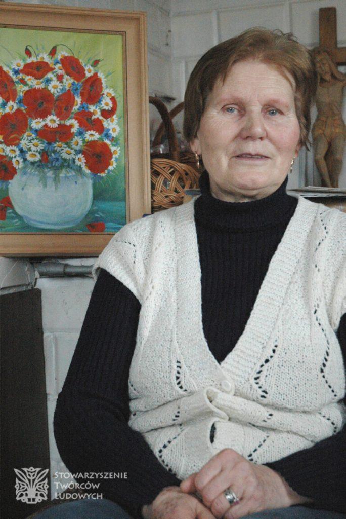 Kobieta siedząca wtle obraz zbukietem kwiatów