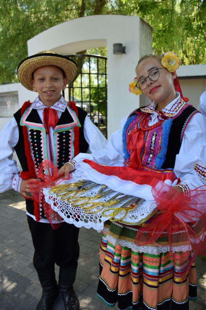 Dzieci wstrojach ludowych trzymające tacę znożycami