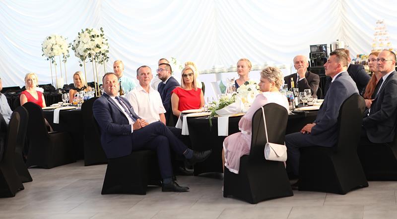 Grupa osó ubrana nagalowo siedząca przy stołach