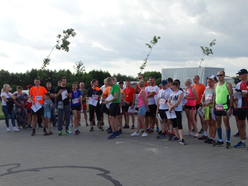 Grupa osób ubrana nasportowo  trzymająca dyplomy pobiegu