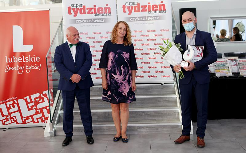 Trzy osoby nazdjęciu trzymające kwiaty