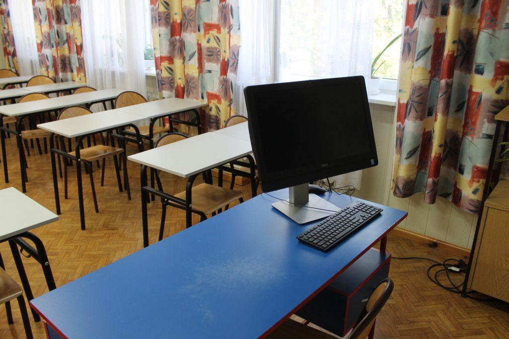 Monitor dokomputera iklawiatura natle ławek szkolnych