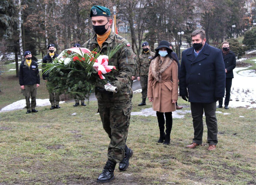 Mężczyzna niesie wieniec zkwiatów, azanim dwie stoją osoby ubrane wubrania wierzchnie