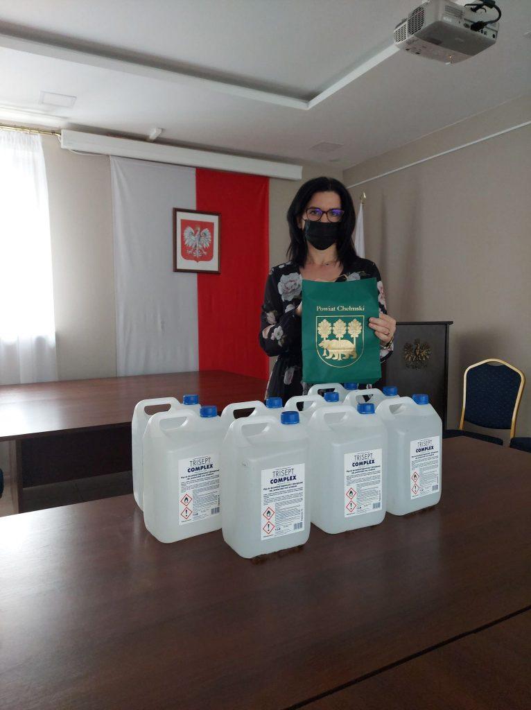 Jedna osoba wpomieszczeniu trzymająca torbę powiatu chełmskiego zupominkiem, nastole stoją płyny dodezynfekcji
