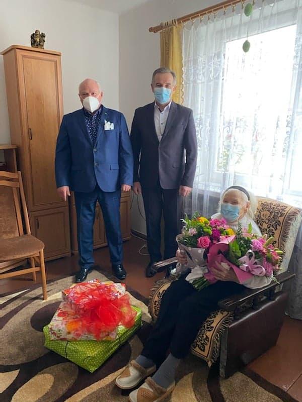 Dwie osoby stojące, jedna osoba siedzi nafotelu itrzyma dwa bukiety kwiatów