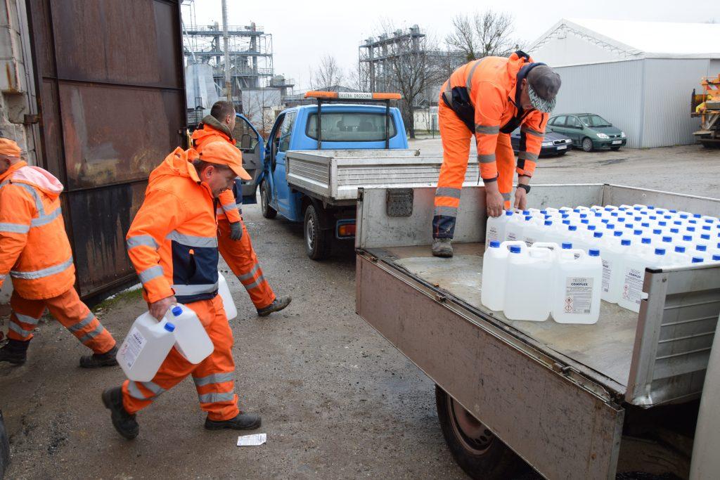 Cztery osoby ładuja nasamochód płyny dodezynfekcji