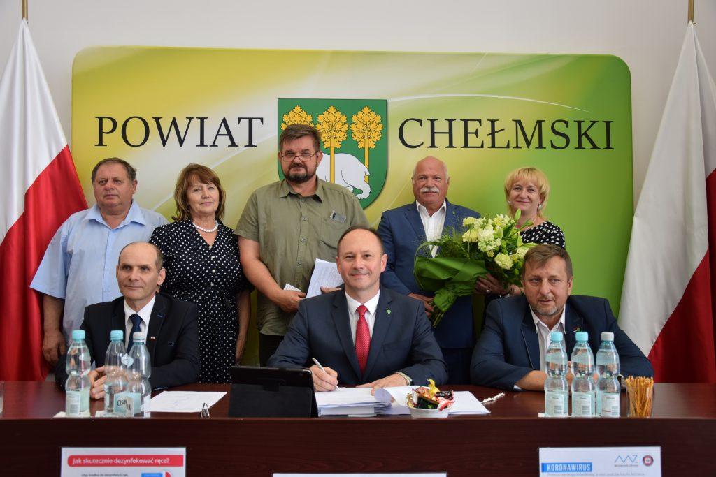 Grupa osób natle zielonego baneru zherbem inapisem Powiat Chełmski