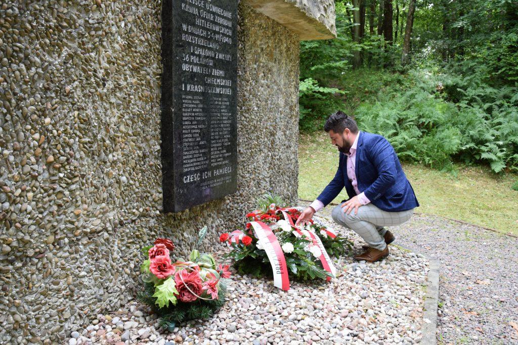 Mężczyzna przedpomnikiem upamiętnającym wydarzenie historyczne. Wieńce kwiatów
