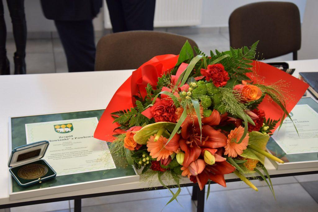 kwiaty orazdyplom orazmedal zasłużony dla powiatu chełmskiego