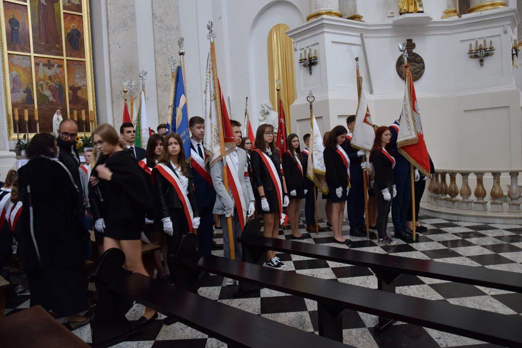 Grupa osób stojąca wkościele zesztandarami